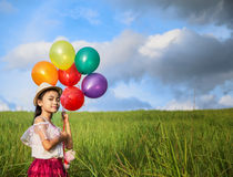Young asia girl holds tightly to a large bunch of helium filled Stock Photo
