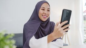 Young Asia muslim businesswoman using smart phone talk to friend by videochat brainstorm online meeting while remotely work from