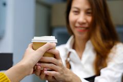 Young asia woman barista serving a diaposable coffee cup with sm Stock Photography