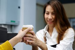 Young asia woman barista serving a diaposable coffee cup with sm Stock Photos