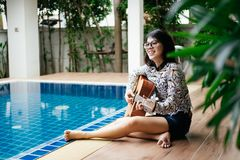 Young woman hold guitar classic in her hand and sitting beside p royalty free stock image
