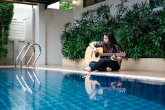 Young woman hold guitar classic in her hand and sitting beside p Stock Photos