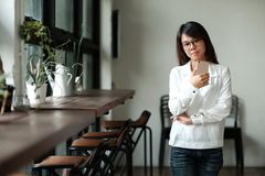 Young woman holding mobile phone and standing by the window. hav. Young asia woman holding mobile phone and standing by the window. have wooden table,chair and Royalty Free Stock Photo
