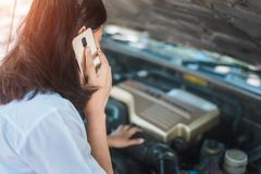 Young asia woman sitting in front of her car, try to calling for assistance with her car broken down royalty free stock images