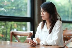 Young women sitting at wooden table in morning and using mobile. Young asia woman sitting at wooden table in morning and using mobile phone. she thinking and Stock Photography