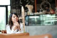 Young women sitting at wooden table in morning and using mobile. Young asia woman sitting at wooden table in morning and using mobile phone. she thinking and Stock Photos