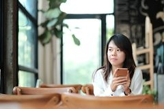 Young women sitting at wooden table in morning and using mobile. Young asia woman sitting at wooden table in morning and using mobile phone. she thinking and Stock Image
