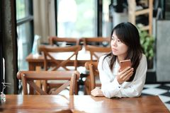 Young women sitting at wooden table in morning and using mobile. Young asia woman sitting at wooden table in morning and using mobile phone. she thinking and Royalty Free Stock Photo