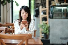 Young women sitting at workplace in morning and using mobile pho. Young asia woman sitting at workplace in morning and using mobile phone for checking something Royalty Free Stock Photography