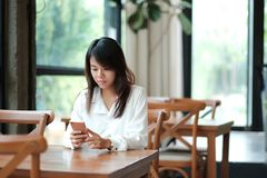 Young women sitting at workplace in morning and using mobile pho. Young asia woman sitting at workplace in morning and using mobile phone for checking something Royalty Free Stock Image