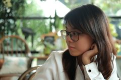 Young woman wearing glasses thinking and waiting someone in coff. Young asia woman wearing glasses thinking and waiting someone in coffee cafe. image for people Royalty Free Stock Image