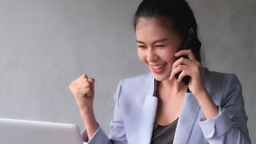 Young Asia women pick up phone and talk with customer on the progress of work