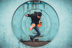 Young Asian active man jumping and kicking action, circle looping wall background. Extreme sport activity concept stock photos