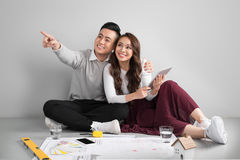 Young asian adult couple sitting on flor planning new home desig Royalty Free Stock Photos
