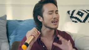 Young asian adult holding microphone and singing. Young asian adult male singer sitting on couch singing rehearsing stock video footage