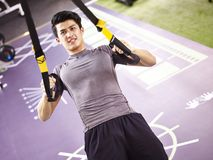 Young asian adult working out in gym. Young asian man exercising in gym using fitness straps Stock Images
