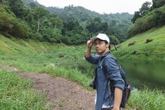 Young Asian adventure man looking at camera with nature green mountain background. Travel lifestyle and relaxation concept.  stock image