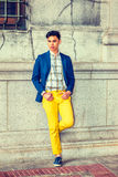 Young Asian American Man in New York. City Boy. Dressing in blue blazer, unbuttoned, patterned under shirt, yellow pants, sneakers, hands on belt loops, rolled Royalty Free Stock Photography