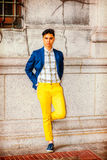 Young Asian American Man in New York. Man Relaxing Outside. Dressing in blue blazer, unbuttoned, patterned under shirt, yellow pants, sneakers, hands on hips, a Royalty Free Stock Photos