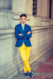 Young Asian American Man in New York. Man Relaxing Outside. Dressing in blue blazer, yellow pants, sneakers, wristwatch, a young handsome guy is standing by old Royalty Free Stock Photography