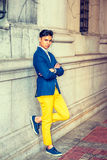 Young Asian American Man in New York. Man Relaxing Outside. Dressing in blue blazer, yellow pants, sneakers, wristwatch, a young handsome guy is standing against Royalty Free Stock Photography