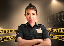 Young Asian American police officer standing serious in custody of crime scene for preserving evidence at do not cross police line royalty free stock image