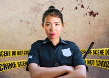 Young Asian American police officer standing serious in custody of crime scene for preserving evidence at do not cross police line royalty free stock photography