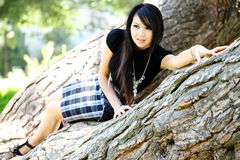 Young Asian American woman in oak tree dress Stock Images