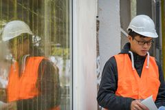 Young Asian engineer at work on construction site. Young Asian apprentice engineer during his work on construction site. Outdoors stock images