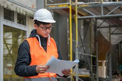 Young Asian engineer at work on construction site. Young Asian apprentice engineer during his work on construction site. Outdoors stock photography