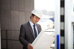 Young asian architect checking plan. Young architect with white helmet holding blueprint checking plan standing front office building Royalty Free Stock Images