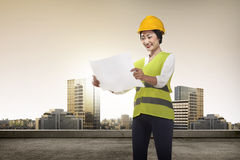 Young asian architect looking the blueprint Stock Photos