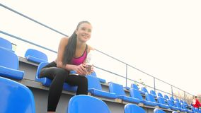 Young asian athlete girl is resting sitting at the stadium on a sunny day. Portrait of young asian woman athlete resting sitting at the stadium after taraining stock video footage