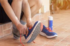 Young asian athlete man tying running shoes in front house,male. Runner ready for jogging on the road outside,wellness and sport concepts Royalty Free Stock Images
