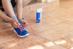 Young asian athlete man tying running shoes in front house,male. Runner ready for jogging on the road outside,wellness and sport concepts Royalty Free Stock Photography