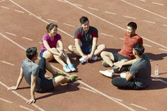 Young asian athletes relaxing on track Royalty Free Stock Image