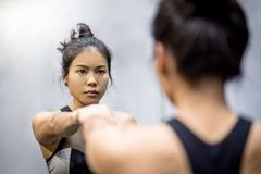 Young asian athletic women in sportswear punching Royalty Free Stock Photography