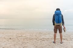 Young Asian backpacker standing on the beach. Young Asian backpacker man standing on the beach and holding hat, summer holiday vacation and travel tropical Royalty Free Stock Images