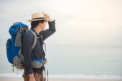 Young Asian backpacker standing on the beach. Young Asian backpacker man standing on the beach and holding hat, summer holiday vacation and travel tropical Stock Image
