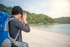 Young Asian backpacker take photos on the beach. Young Asian backpacker man take photos of beautiful tropical beach and sea by camera, background for summer Royalty Free Stock Images