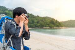 Young Asian backpacker take photos on the beach. Young Asian backpacker man take photos of beautiful tropical beach and sea by camera, background for summer Royalty Free Stock Photo