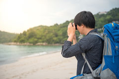 Young Asian backpacker taking photos on the beach. Young Asian backpacker man taking photos of beautiful tropical beach and sea by camera, background for summer Stock Images