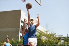 Young asian men playing basketball. Young asian basketball player going up for a layup while opponent playing defense stock photography