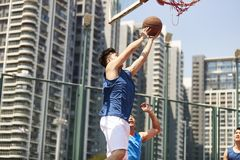 Young asian men playing basketball. Young asian basketball player going up for a layup while opponent playing defense stock photos