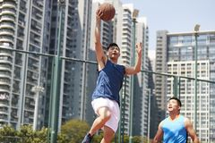Young asian men playing basketball. Young asian basketball player going up for a layup while opponent playing defense stock image