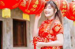 Young asian beautiful girl in chinese traditional red dress smile stand near china lamp, in the Chinese New Year. Festivities. Young asian beautiful girl in stock photo