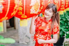 Young asian beautiful girl in chinese traditional red dress smile stand near china lamp, in the Chinese New Year. Festivities. Young asian beautiful girl in royalty free stock photos