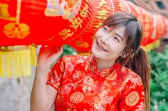 Young asian beautiful girl in chinese traditional red dress smile stand near china lamp, in the Chinese New Year. Festivities. Young asian beautiful girl in stock image