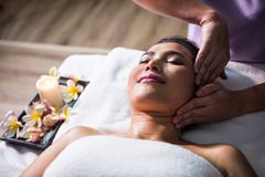 Thai oild massage at face. Young Asian beautiful woman in spa club. Body care treatment by Thai oil. Cute girl massage at face by professional massager hands Stock Image