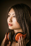Young Asian beauty with stereo headphones. Around her neck staring off into space with a dreamy expression of relaxation and pleasure, closeup side view of her stock image